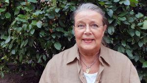 Kristina Heikel från pensionärsförbundet framför en vägg av växter