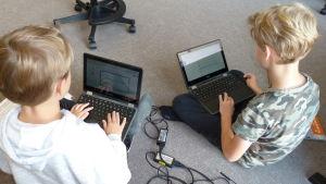 Kaksi oppilasta tekee tietokoneilla töitä luokan lattialla.