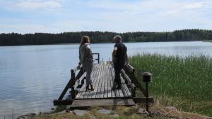 Två personer, en kvinna och en man, står på en lång brygga och tittar ut mot havet.