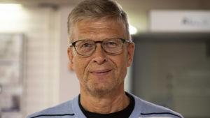 Mansperson i ljusblå tröja och glasögon tittar leende in i kameran.