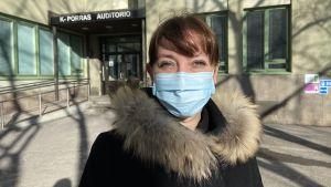 Ann-Sofie står i vårsolen iklädd vinterjacka och munskydd.