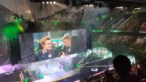 En arena fylld med folk. I mitten syns en stor skärm som visar två män som ser emotionella ut.