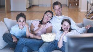Mamma, pappa, son och dotter sitter i soffan och ser på tv