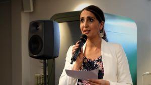 Nasima Razmyar håller i en mikrofon och talar.