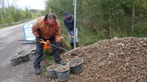 Roope Rehbinder skyfflar grus i ämbar vid sidan av en väg.