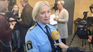 En kvinna står och blir intervjuad