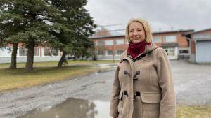 Kvinna poserar framför skolbyggnad