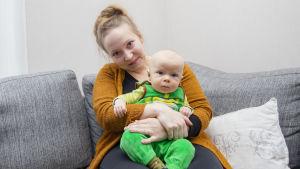 nainen istuu lapsenkanssa sohvalla