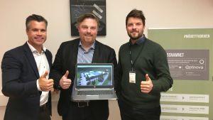 Tre män visar tummen upp, mannen i mitten håller en laptop i handen.