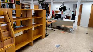 Tomma bokhyllor i ett bibliotek.