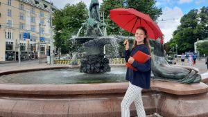Maria Aho står med ett rött paraply framför Havis Amanda.