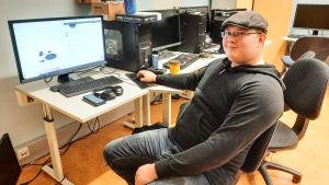 En ung man sitter framför en dator.