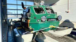 En grön hydrokopter. Fordonet har pontoner som medar och en motor bak på.