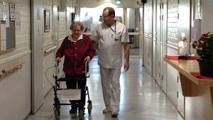 Närvårdare Karl-Erik Dahlin går genom korridoren med Doris som går med rullator.