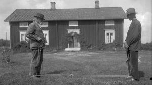 """Två män leker """"dra girsnot"""", där man ska försöka få omkull sin motståndare genom att dra i ett rep som är fastspänt mellan de tävlandes vrister. Bilden är tagen 1930 i Finström, Åland."""