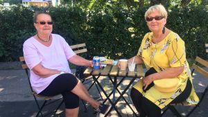två kvinnliga åbobor som dricker kaffe vid åstranden