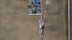 Gatukonstnären Banksys väggmålning föreställande ett öppet fönster med men kvinna och svartsjuk man som tittar ut medan kvinnans älskare i smyg hänger från ena handen på utsidan av fönstret.