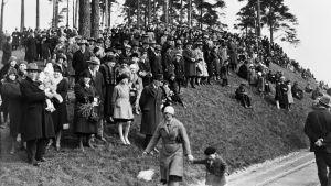 En folksamling på en kulle. Bilden är svartvit och mäniskorna är iklädda gammalmodiga kläder.
