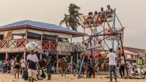 Strand i Nigeria som kryllar av människor. På bilden syns hus och ett hemgjort litet pariserhjul.