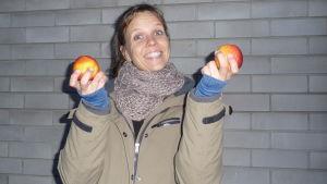En skrattande och spexande Petra Österberg med ett rött äpple i var hand. I övrigt grå bakgrund och rätt mörka färger.