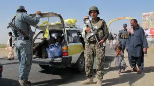 Soldater söker igenom en bil som användes av en familj på flykt undan strider i Sangin i Helmand-provinsen i södra Afghanistan.
