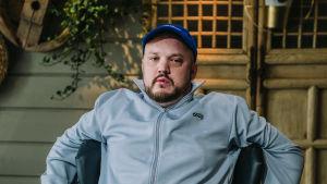 Rap-artisti Pyhimys istuu sisätiloissa Vain elämää -ohjelman kuvauksissa. Nojaa käsillään tuolin selkänojaan.