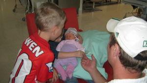 Liinu sairaalassa perheensä kanssa, siskonsa sylissä