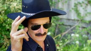 Kent från Jeppis pappa Guy i svarta kläder och svart cowboyhatt och svarta solglasögon.