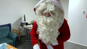 en utklädd jultomte i rött med vitt krullgit skägg