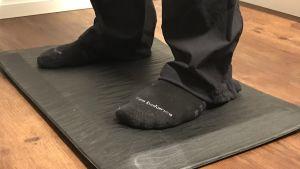 fötter på en ergonomisk matta