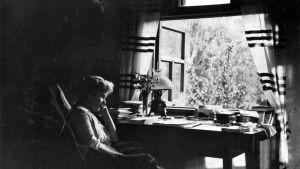 Hagar Olssson sitter i stol i ett arbetsrum, lutar mot handen. Skrivbord, böcker och fönster öppet i bakgrunden. På gården träd.