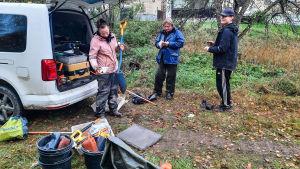Tre personer i täckjackor packar ihop saker i en paketbil.