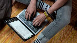 En person sitter med datorn framför sig på golvet.