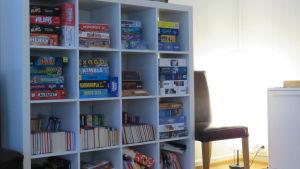 En hylla full med olika brädspel och en del böcker.