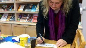 """Katarina Norling skriver ordet """"språk"""" på en lapp."""