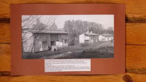 ett svartvit foto på en brun stockvägg. Fotografiet föreställer Ekobyn Näckrosen i Bromarv kyrkoby.
