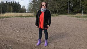 Kvinna iklädd solglasögon och stövlar står på en stran en vårdag.