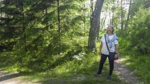 En kvinna står i en skog. Hon ser glad ut, vädret är somrigt.