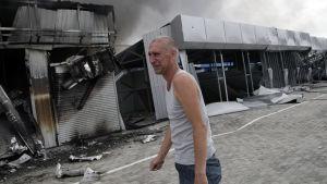 Man utanför sin förstörda affär i Donetsk.