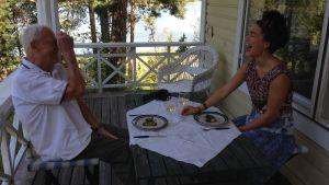 Caj Bremer ja Meeri Koutaniemi nauravat ruokapöydässä Kaptensuddenissa. Kuva dokumenttielokuvan Caj Bremer, valokuvaaja kuvauksista.