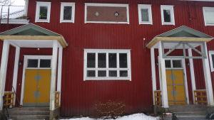 Fasadbild på Vill Christine, en gammal skolbyggnad med rödmyllad brädfodring och senapsgula ytterdörrar.