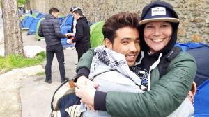 En man och en kvinna ger varandra en kram framför en rad tält.