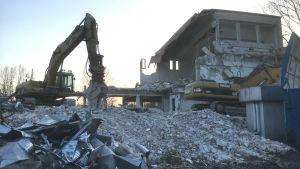En riven byggnad, högar med bråte och en grävmaskin.