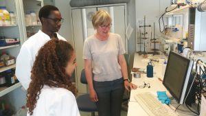 Tre forskare, två kvinnor och en man, står och pratar med varandra i ett forskningslaboratorium.
