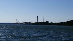 De två skorstenarna på Fortums kolkraftverk syns mot en blå himmel.