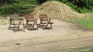 Tre solstolar/bruna utestolar av trä på en sandstrand. Sommar och sol. En hög med krattad, fjolårsvas i bakgrunden.