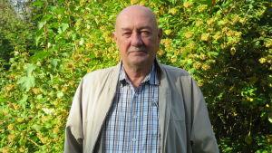 En äldre man med rakat huvud, rutig skjorta och beige jacka står ute. Solsken. Höst. Bakom en grönbladig, stor buske