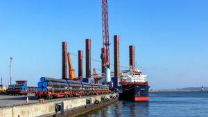 Rörlängder väntar på lastning på kajen. Ett fartyg väntar på att lastas.