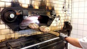 Två färdiga bröd tas ut ur ugnen.