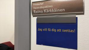 """Skylt på väggen där det står fritidschef Reino Kärkkäinen och under det """"Jag vill få dig att svettas""""."""